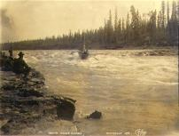 Boat navigating Whitehorse Rapids on the Yukon River, Yukon Territory, 1898.