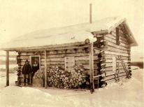Mr. and Mrs. Mogridge in doorway of their cabin, Dawson, Yukon Territory, ca. 1899.