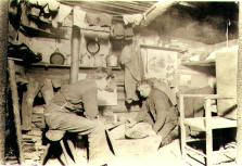 Two miners inside of cabin sampling dirt for gold using mining pan, Yukon Territory, ca. 1898