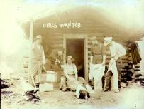 Posed scene with five Klondikers engaged in domestic activities outside of cabin, Yukon Territory,...