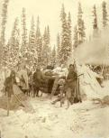 Hunters with rifles and snowshoes outside of log cabin, Yukon Territory, ca. 1898.