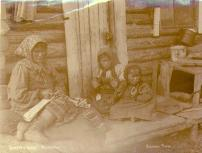 Indian woman with two children fashioning hide artifacts outside of cabin, Moosehide, Yukon...