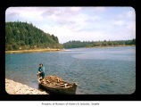 Cynthia Davis seated on the outboard engine of a canoe on the Quileute Indian Reservation