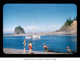 Men setting a fishing net while children watch on the Quileute Indian Reservation
