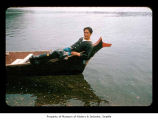 Harvey Eastman on the bow of a canoe, probably on or near the Quileute Indian Reservation