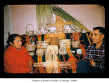 Agnes and William Penn near a basket display, probably in a house on the Quileute Indian...