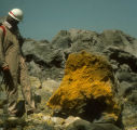 Bill Rose looking at sulfur on lava boulder