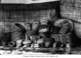 Native American baskets in front of hanging cedar mats, probably from the Makah Tribe