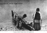 Native American man with fish and a canoe, probably on an Olympic Peninsula beach