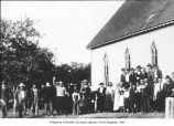 People, mostly Native Americans, standing outside a church, probably in Jamestown