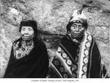 Native American man and woman sitting in front of rock, probably on the Olympic Peninsula