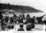 People, mostly Native Americans, sitting among beached canoes at Neah Bay