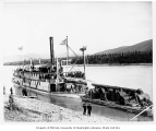 Steamer MONARCH with passengers on deck and lighter at river landing, ca. 1904
