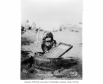 Eskimo child with wooden tub and washboard, ca. 1905