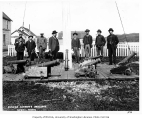 Group of men standing next to Russian cannons, Unalaska, n.d.