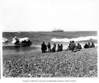 Yupik people on beach at Whalen, Siberia, with Steamship CORWIN in distance, 1907