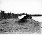 Fish drying rack and overturned boat for shelter on the shore of the Kuzitrin River, ca. 1904