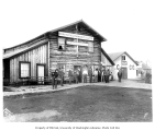 People in front of log building with signs for Northern Commercial Co. and McQuesten & Co.,...