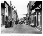 Ketchikan board street, with people and storefronts, including signs for Dr. Zuber, Dentist,...