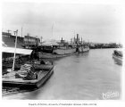 Stern wheel steamer SCHWATKA and barge MINK at Pioneer Dock in Fairbanks, with California Saloon...