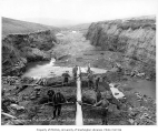 Men shoveling dirt into flume at mining operation, Buster Creek, near Nome, 1906