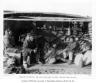 Eskimo family sitting beneath upturned umiak, Alaska, ca. 1904