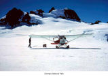 Fairchild airplane at Snow Dome where a man appears to be retrieving parcels, Olympic National...