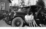 Young women and a man seated on the running board of a car parked outside a house, possibly on the...