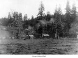 Oil well and small buildings, possibly on the Olympic Peninsula, 1913
