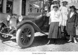 Women standing near a car outside a house, possibly near Mora, ca. 1925