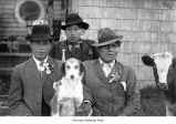 Native American men wearing hats and suits with a dog and a cow outside a building covered with...