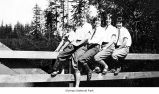 Girls on a fence near woods, possibly on the Olympic Peninsula, date unknown