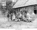 Group portrait of teachers and students next to a schoolhouse possibly in Port Hadlock, date...