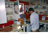 Researcher in the kitchen of the IGY station, probably on Mount Olympus, Olympic National Park,...