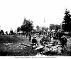 Military corral in Seattle showing soldiers resting with their equipment, August 1900