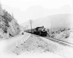 Great Northern Oriental Limited train and tracks beside a highway, ca. 1931