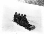 Four women on sled in the snow, Leavenworth, ca. 1931