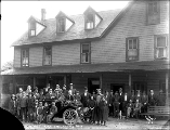 Group of people posed with automobile in front of the Index Hotel, Index, October 1911