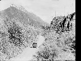 Automobile on highway near Castle Rock, west of Mt. Baring, ca. 1925