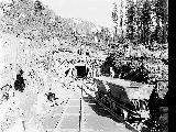 West portal of the Cascade Tunnel showing construction workers and muck cars, Scenic, March 16,...