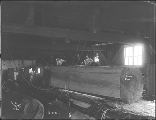 Sawmill interior showing large cut log and workers, Grotto, ca. 1911