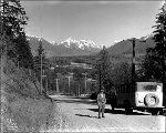 Man and vehicle on road in the Skykomish Valley with view toward Sultan, 1927