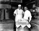 Chef and baker at west portal with cake celebrating breakthrough, May 1, 1928