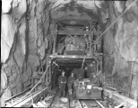 Concrete machine and workers inside tunnel, ca. 1928