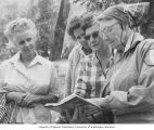 Seattle Audubon Society Field Day showing Hazel Wolf and others looking at a field guide, May 1966
