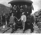 Asahel Curtis and other notable dignitaries standing on and around a railroad car, n.d.