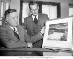 Joseph Drumheller and Richard Downing looking at a photograph of the Grand Coulee Dam, Spokane,...
