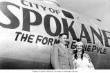 Joseph Drumheller and Miss Spokane wearing Native American dress standing in front of a airplane,...