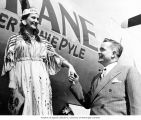 Joseph Drumheller holding Miss Spokane's hand with her dressed in Native American costume, in...