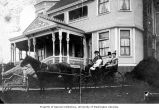 George Kinnear, his wife Angie and others in a horse-drawn buggy in front of the Kinnear home,...